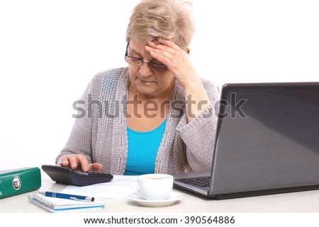 Worried senior woman, an elderly pensioner counting utility bills at her home, concept of financial security in old age - stock photo