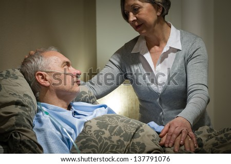 Worried senior woman caring with sick husband in the bedroom - stock photo
