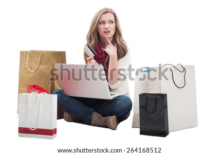 Worried shopping woman holding card and thinking what else to buy online using laptop - stock photo