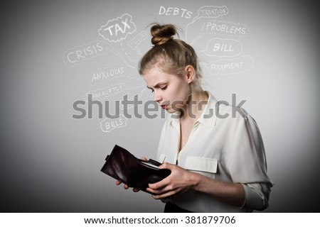 Worried slim woman is looking at an empty wallet. Poverty, taxes, debts and other problems.