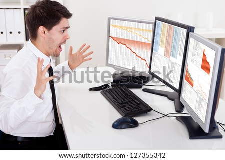 Worried stock broker looking at stock charts going down - stock photo
