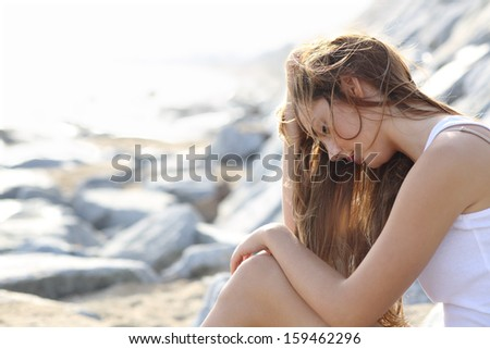Worried teenager girl on the beach sitting on the sand               - stock photo