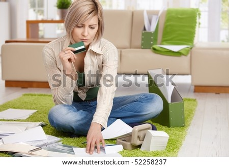 Worried woman checking documents, holding credit card, sitting on floor with crossed legs at home. - stock photo