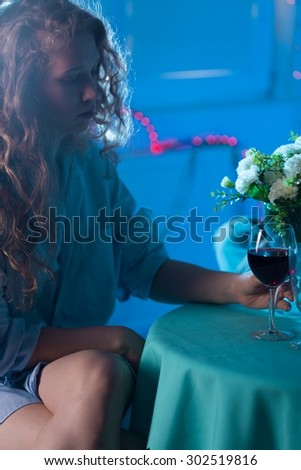Worried woman drinking wine - blue picture - stock photo