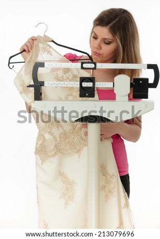 Worried woman holding a bridal dress on a medical weight scale. - stock photo