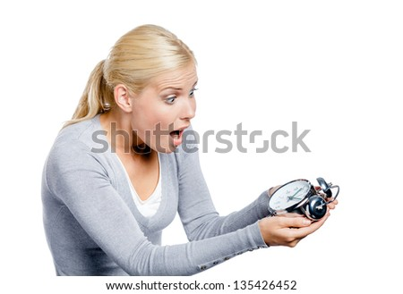 Worried woman in grey pullover looks at the alarm clock, isolated on white