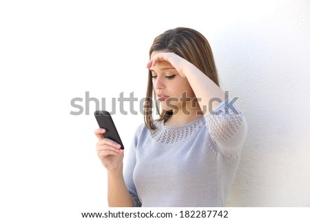 Worried woman looking at the mobile phone on a white wall isolated           - stock photo