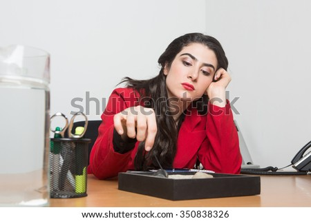 Worried woman sitting in the office playing with zen garden sand while thinking, she has her hand in her head and is wearing a red jacket