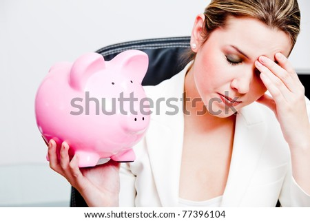Worried woman with her savings in a piggy bank ? isolated