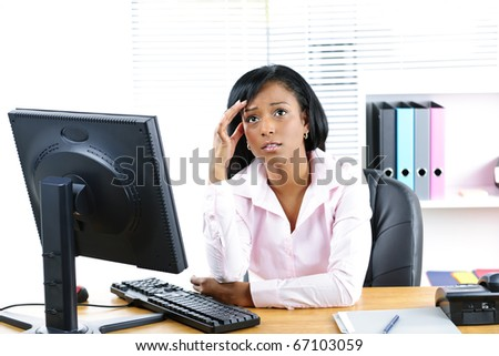 Worried young black business woman at desk in office - stock photo