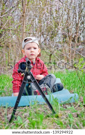 Worried young boy sitting on a mat on the ground in the countryside beside a tripod mounted rifle with a scope attached as he waits for his Dad - stock photo