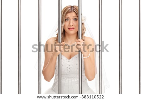 Worried young bride standing behind bars in jail isolated on white background - stock photo