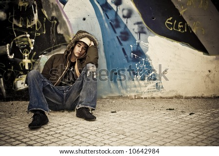 Worried young male on urban background - stock photo