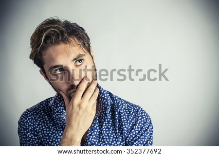 Worried young man looks up at copy space - stock photo