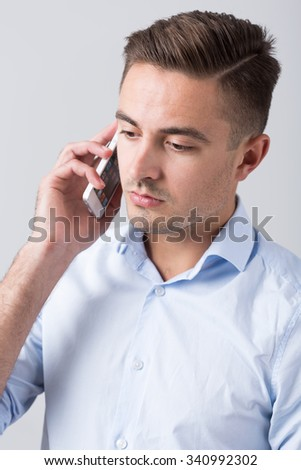 Worried young office worker with mobile phone - stock photo