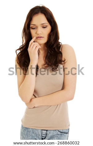 Worried young thoughtful woman looking down. - stock photo