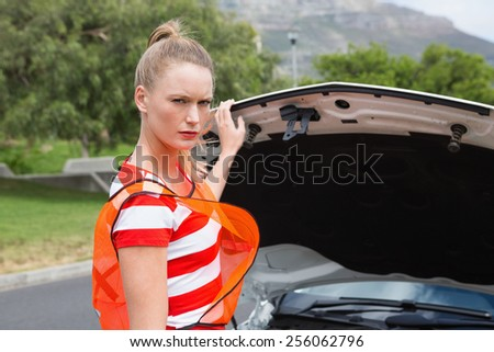 Worried young woman beside her broken down car in the street - stock photo