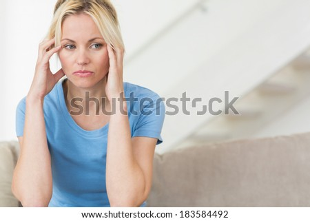 Worried young woman sitting in the living room at home - stock photo