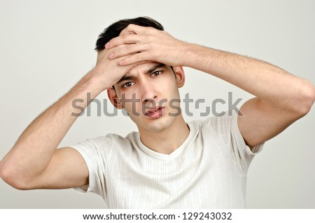Worry, sadness, desperation. Young man holding his head frowning with worry. Man with different facial  expressions. - stock photo
