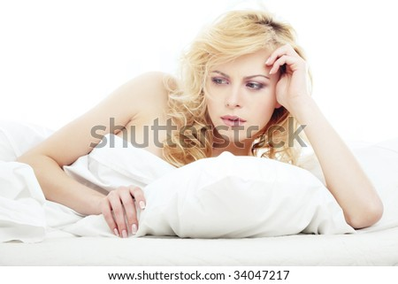 Worry thinking lady on the white bed - stock photo