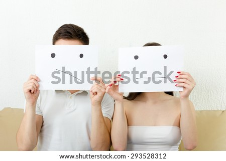 Worrying young couple  is very concerned and having troubles. Teenagers in despair. Unhappy persons sitting on couch. Man and woman cover their faces with sad smiley  drawn on paper with one tear. - stock photo