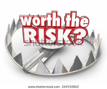 Worth the Risk red 3d words on a steel bear trap to illustrate danger and hazard that might not be worth the bad outcome - stock photo