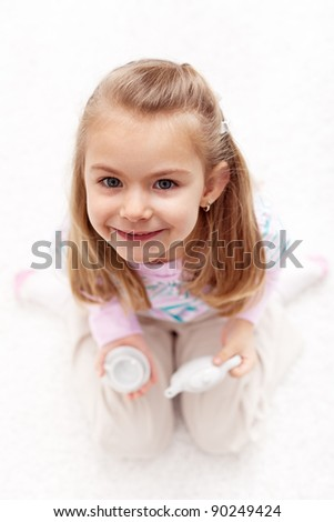 Would you care for a cup of tea - little girl playing at home - stock photo