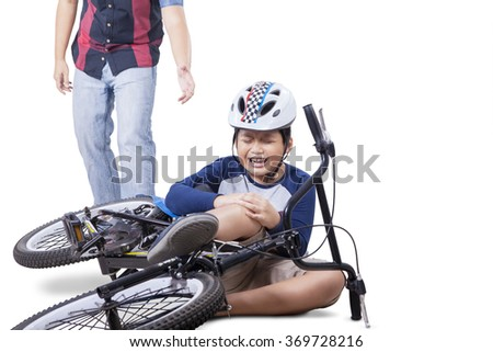 Wounded child falling from his bike and crying while holding his knee with dad coming to help, isolated on white