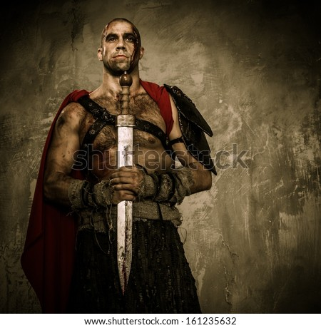 Wounded gladiator holding sword covered in blood with both hands - stock photo