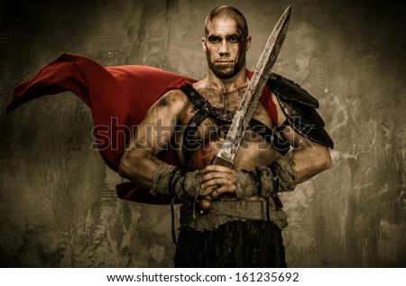 Wounded gladiator in waving coat holding sword covered in blood  - stock photo