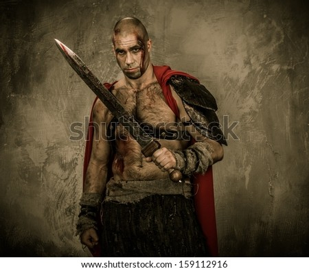 Wounded gladiator with sword covered in blood - stock photo