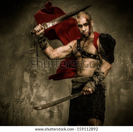 Wounded gladiator with two swords covered in blood  - stock photo