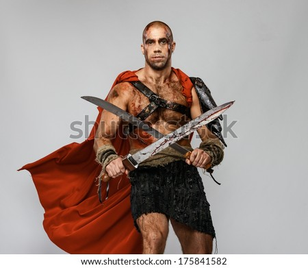 Wounded gladiator with two swords covered in blood isolated on grey