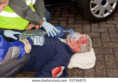 Wounded man after car crash being resuscitated with oxygen mask - stock photo