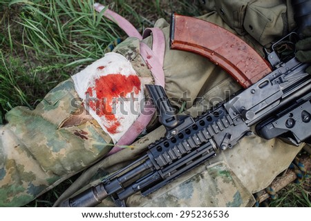 Wounded russian soldier  in the forest awaiting medical assistance - stock photo