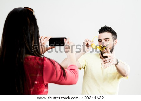 wounded-up couple taking photographs with their smartphones