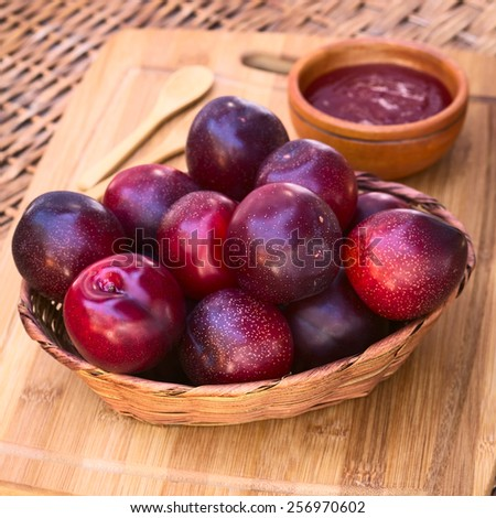 Woven basket filled with satsuma plum with small bowl of plum jam in the back on wooden board photographed with natural light (Selective Focus, Focus on the plums in the front) - stock photo