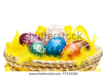 Woven basket full of colorful eggs. Isolated on a white background.