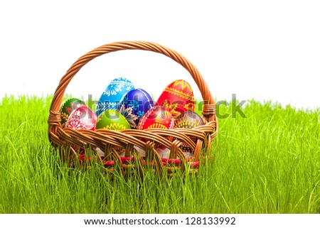 Woven basket full of colorful eggs on green grass