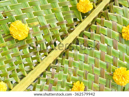 Woven coconut leaves with yellow flower - stock photo