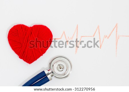 woven red heart and the stethoscope on the cardiogram - stock photo