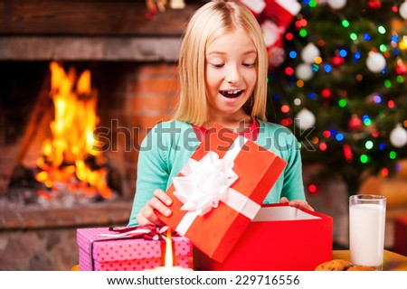 Wow! Cute little girl opening a gift box and smiling while sitting at the table with Christmas Tree and fireplace in the background  - stock photo