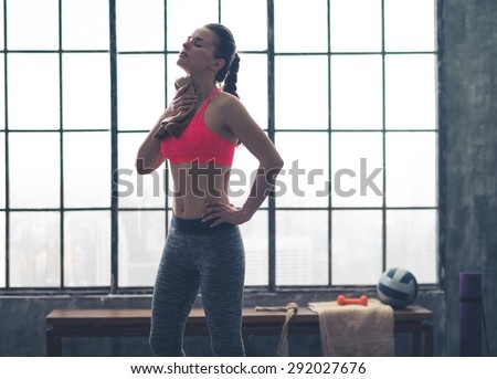 Wow, that felt good. A woman wipes hard-earned sweat off her neck after a great workout. - stock photo