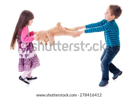 Wrangling boy and girl pulling apart toy bear - stock photo