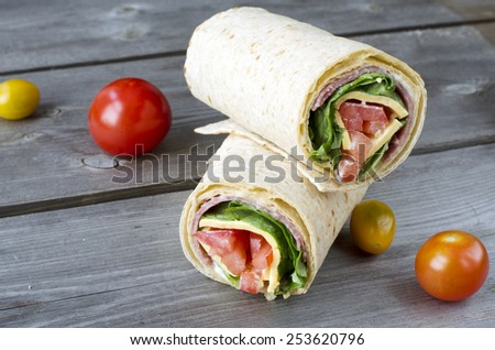 wrap sandwich with salami, lettuce, tomatoes and cheeses - stock photo