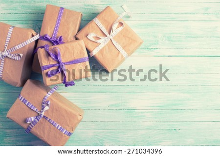 Wrapped boxes with presents on turquoise painted wooden planks. Selective focus. Place for text. Toned image. - stock photo