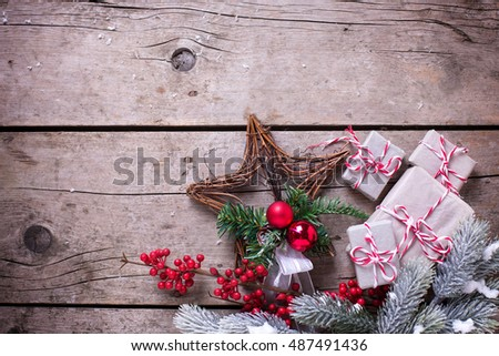 Wrapped christmas presents, fur tree branches, red berries on aged wooden background. Selective focus. Place for text.