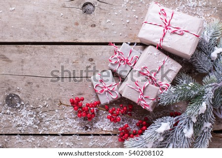 Wrapped christmas presents, fur tree branches, red berries on  wooden background. Selective focus. Place for text.
