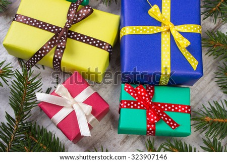 Wrapped colorful gifts for Christmas, birthday or other celebration and green spruce branches on old white wooden plank