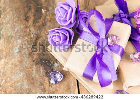 Wrapped gift boxes with presents and decorative flowers on aged wooden background. Place for text. - stock photo